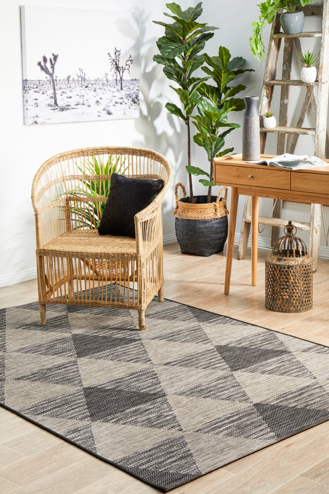 Terrace Rug colour black with rattan furniture and indoor plants